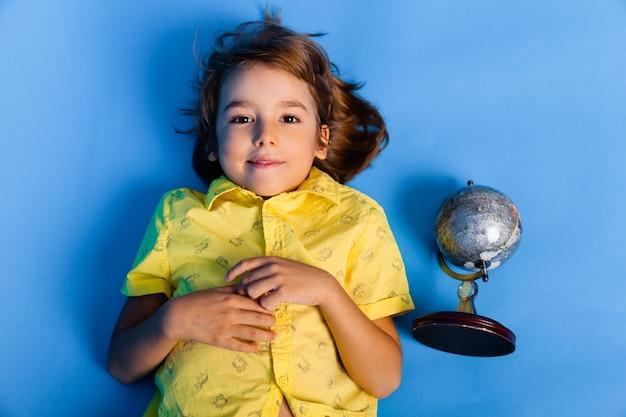 Ragazzo sorridente sdraiato su sfondo blu con globo
