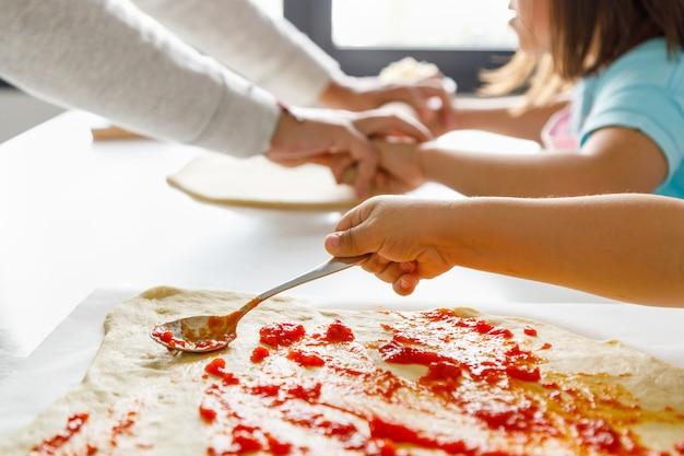 Giovane ragazzo cucchiaio di pomodoro su un impasto per pizza mentre sua madre impasta un'altra pizza con sua sorella