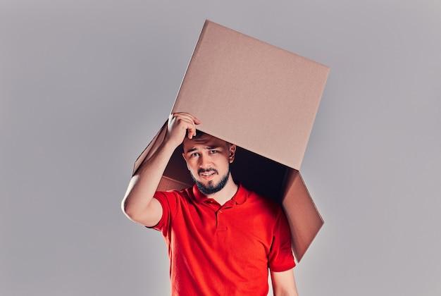 Ragazzo in piedi e gesticolando con una scatola di cartone sulla testa.