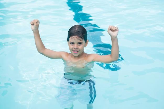 Giovane ragazzo in piedi con le braccia in alto in piscina