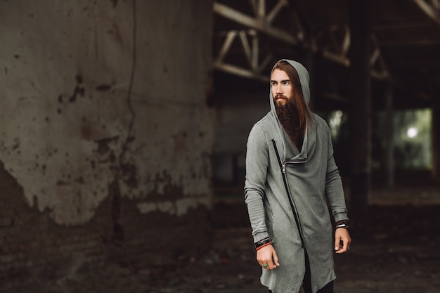 Il ragazzo si trova in un edificio abbandonato. ragazzo errante il ragazzo è vestito con abiti eleganti, ha una lunga barba.