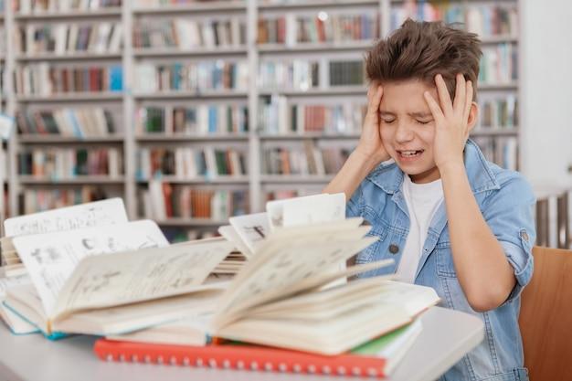 Giovane ragazzo che si agita sopra la pila di libri e di libri di testo sulla sua scrivania