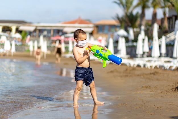 Giovane ragazzo in pantaloncini da bagno e pistola giocattolo con maschera medica sulla spiaggia che si protegge dal virus corona