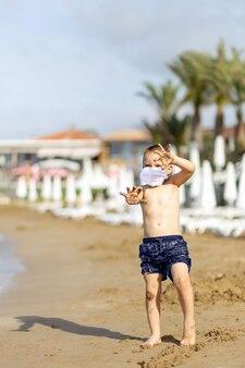 Giovane ragazzo in pantaloncini da bagno con maschera medica sulla spiaggia che si protegge dal virus corona, covid-19