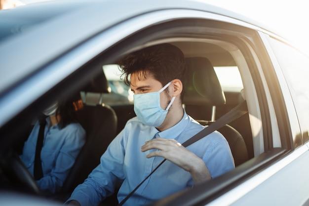 Ragazzo giovane tassista allacciare la cintura di sicurezza indossando maschera medica sterile.