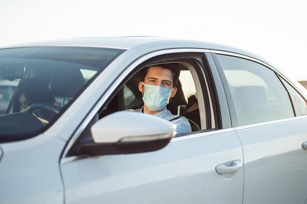 Il tassista del ragazzo dà al passeggero un giro che indossa una mascherina medica sterile