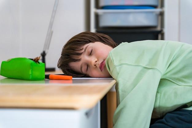 Ragazzo di dieci anni che fa i compiti seduto al tavolo di casa. bambino stanco addormentato quando fa esercizi scolastici si affaccia sulla scrivania.