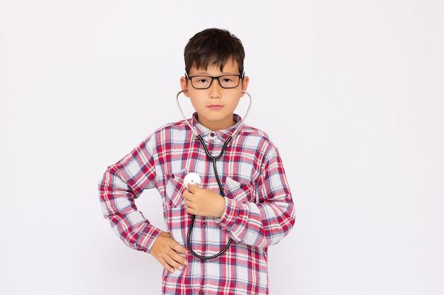 Ragazzo che cerca di ascoltare il suo cuore che gioca con uno stetoscopio