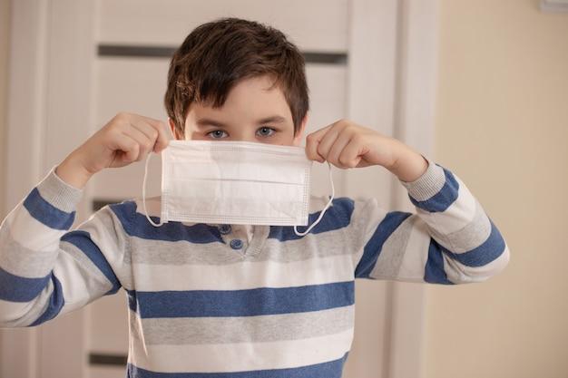 Giovane ragazzo con la faccia protetta con maschera medica tiene nelle sue mani