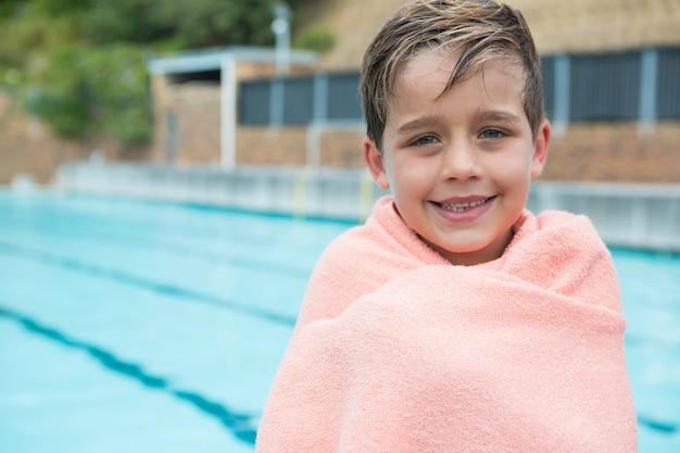 Ragazzo giovane avvolto in un asciugamano in piedi a bordo piscina