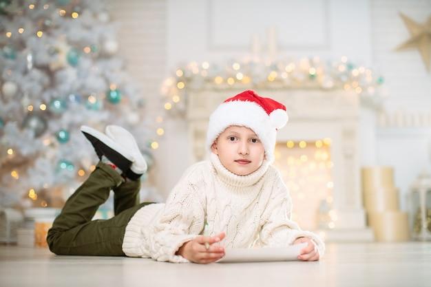 Ragazzo che scrive una lista dei desideri sul pavimento con decorazioni natalizie in background