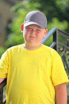 Un ragazzo con una maglietta gialla, un berretto e occhiali da sole si trova nella natura. foto di alta qualità