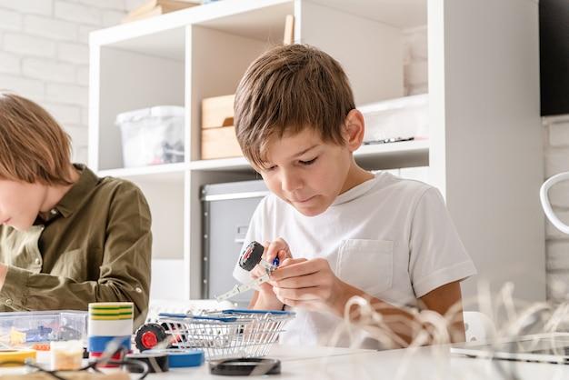 Ragazzi giovani e divertirsi costruendo insieme auto robot in officina
