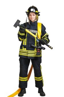 Giovane donna coraggiosa in uniforme di vigile del fuoco con manichetta antincendio e mazza
