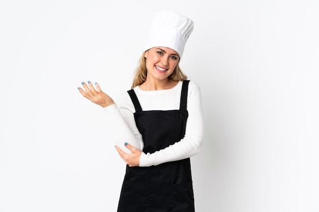 Giovane donna chef brasiliana isolata su bianco che estende le mani a lato per invitare a venire