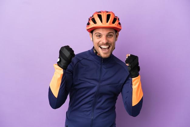 Giovane ciclista brasiliano uomo isolato su sfondo viola che celebra una vittoria nella posizione del vincitore