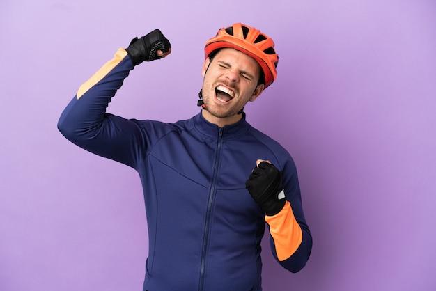 Giovane ciclista brasiliano uomo isolato su sfondo viola che celebra una vittoria