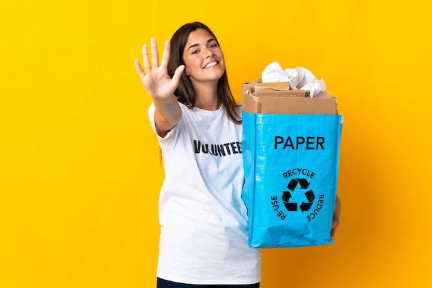 Giovane ragazza brasiliana che tiene un sacchetto di riciclaggio pieno di carta da riciclare isolato su sfondo giallo contando cinque con le dita