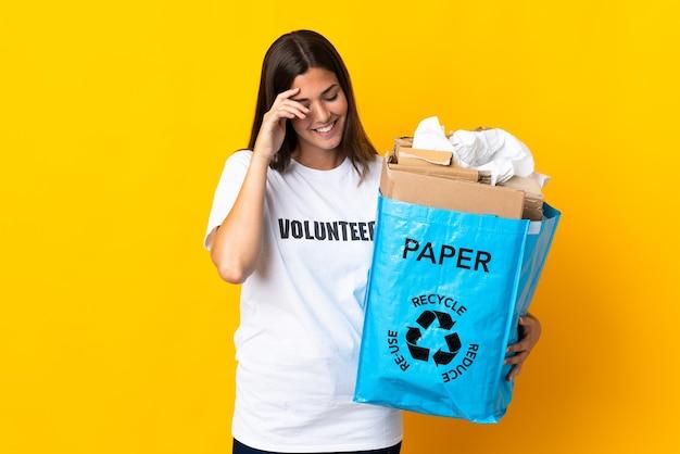 Giovane ragazza brasiliana che tiene in mano un sacchetto di riciclaggio pieno di carta da riciclare isolato su sfondo giallo ridendo