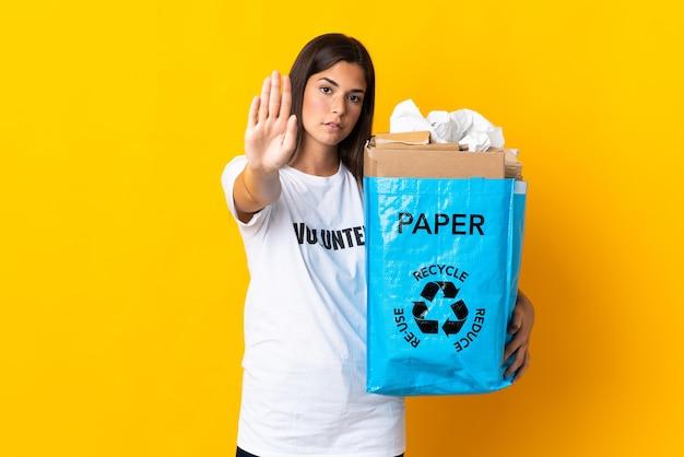 Giovane ragazza brasiliana che tiene un sacchetto di riciclaggio pieno di carta da riciclare isolato su priorità bassa gialla che fa gesto di arresto