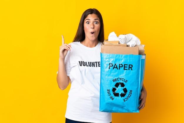 Giovane ragazza brasiliana che tiene un sacchetto di riciclaggio pieno di carta da riciclare isolato