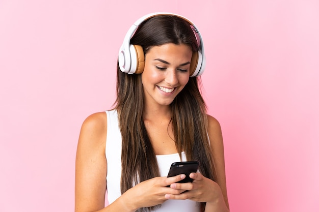 Giovane ragazza brasiliana isolata sulla musica d'ascolto rosa e guardando al cellulare