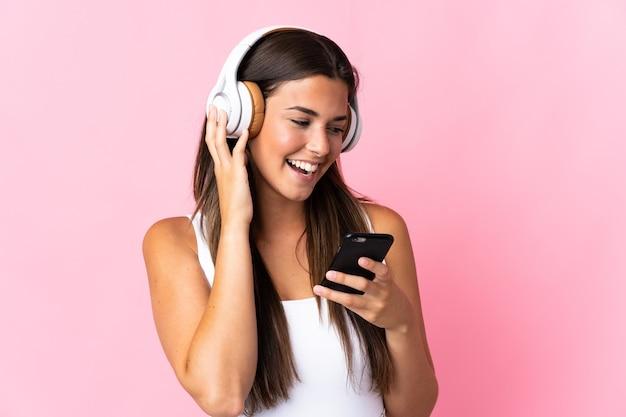 Giovane ragazza brasiliana isolata sulla musica d'ascolto della parete rosa con un cellulare e cantando