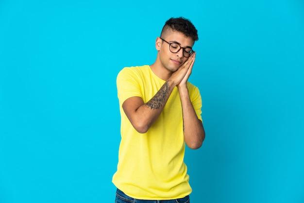 Giovane uomo brasiliano su sfondo blu che fa gesto di sonno nell'espressione dorable