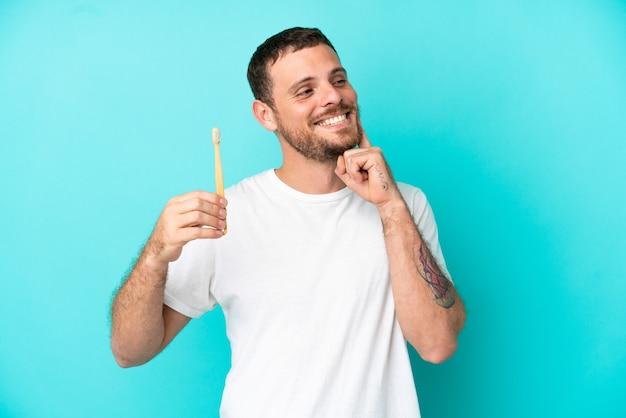 Giovane uomo brasiliano che si lava i denti isolati su sfondo blu pensando a un'idea mentre guarda in alto