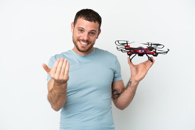 Giovane brasiliano che tiene in mano un drone isolato su sfondo bianco che invita a venire con la mano. felice che tu sia venuto