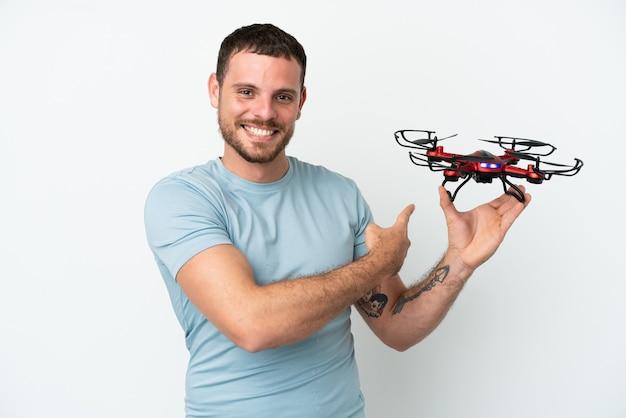 Giovane brasiliano che tiene un drone isolato su sfondo bianco che punta indietro