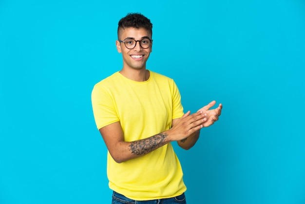 Giovane uomo brasiliano isolato sulla parete blu che applaude