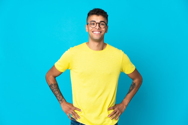 Giovane uomo brasiliano isolato sulla parete blu in posa con le braccia all'anca e sorridente