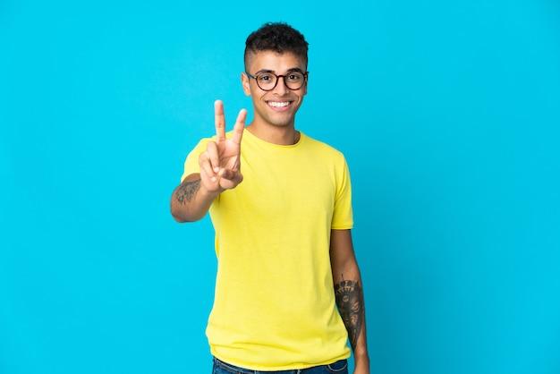 Giovane uomo brasiliano isolato sulla parete blu che sorride e che mostra il segno di vittoria