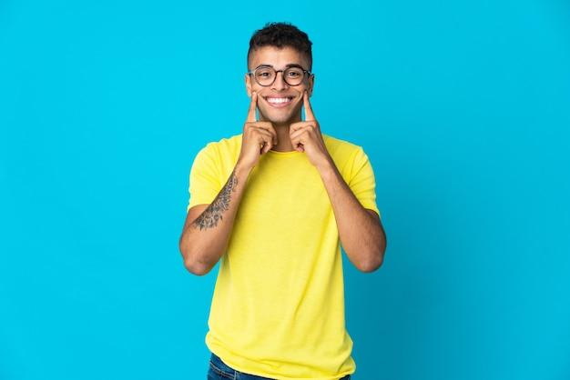 Giovane uomo brasiliano isolato sulla parete blu che sorride con un'espressione felice e piacevole
