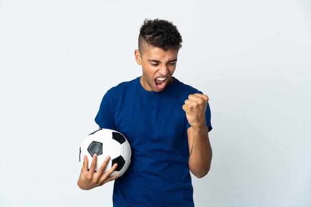 Giovane brasiliano sopra la parete isolata con pallone da calcio che celebra una vittoria