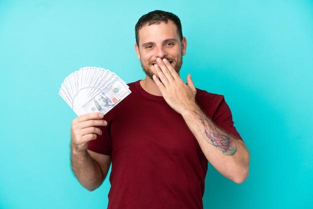 Giovane brasiliano che prende un sacco di soldi su sfondo isolato felice e sorridente che copre la bocca con la mano