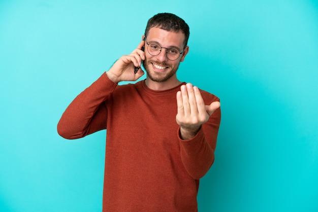 Giovane brasiliano che utilizza il telefono cellulare isolato su sfondo blu che invita a venire con la mano. felice che tu sia venuto