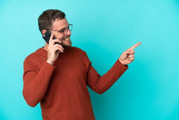 Giovane brasiliano che usa il telefono cellulare isolato su sfondo blu puntando il dito di lato e presentando un prodotto
