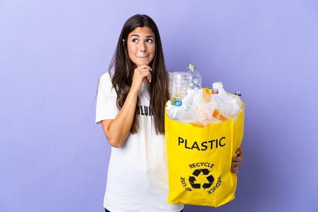 Giovane donna brasiliana che tiene un sacchetto pieno di bottiglie di plastica da riciclare isolato su viola avendo dubbi e pensando