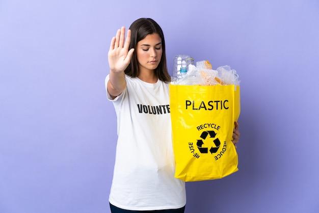 Giovane donna brasiliana che tiene un sacchetto pieno di bottiglie di plastica da riciclare isolato su viola facendo gesto di arresto e deluso