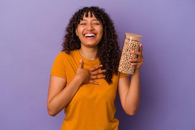 La giovane donna brasiliana che tiene una bottiglia di ceci isolata sulla parete viola ride ad alta voce tenendo la mano sul petto.