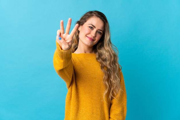 Giovane donna brasiliana isolata sull'azzurro felice e contando tre con le dita