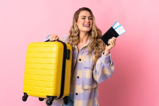 Giovane donna brasiliana isolata su sfondo rosa in vacanza con la valigia e il passaporto