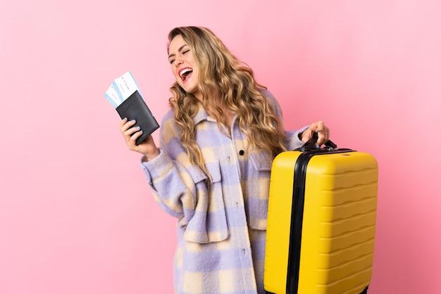 Giovane donna brasiliana isolata sul rosa in vacanza con la valigia e il passaporto