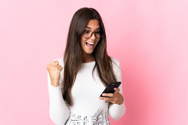 Giovane donna brasiliana isolata sulla parete rosa sorpresa e l'invio di un messaggio