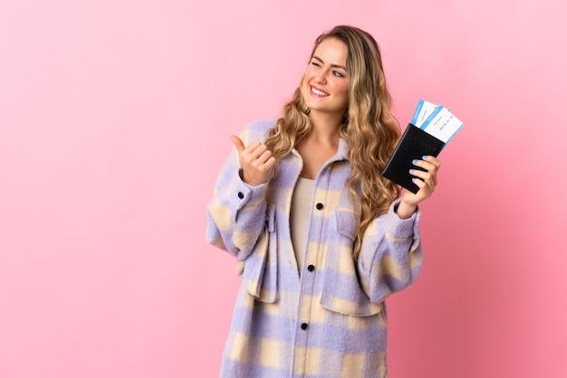 Giovane donna brasiliana isolata sulla parete rosa in vacanza in possesso di un passaporto e aereo con il pollice in su