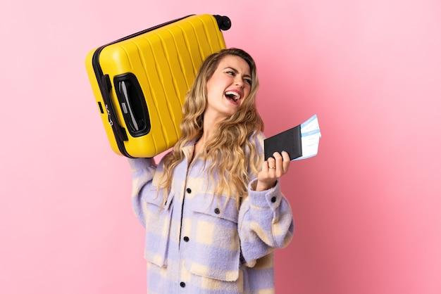 Giovane donna brasiliana isolata sul muro rosa in vacanza con la valigia e il passaporto