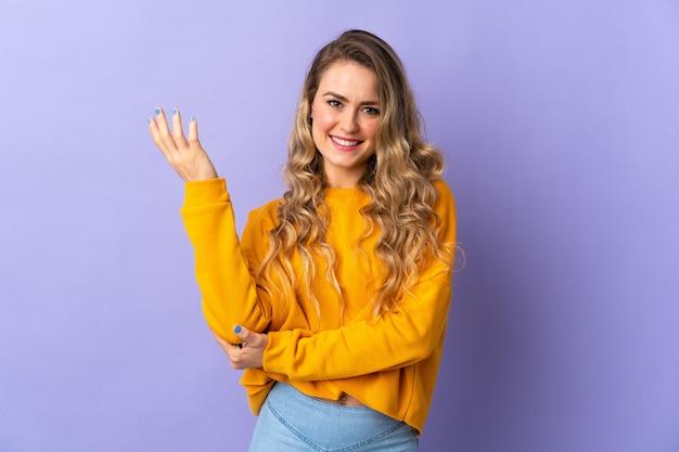Giovane donna brasiliana isolata su sfondo viola che estende le mani di lato per invitare a venire Foto Premium