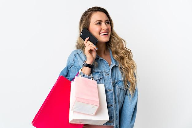 Giovane donna brasiliana isolata su bianco che tiene i sacchetti della spesa e chiama un amico con il suo telefono cellulare
